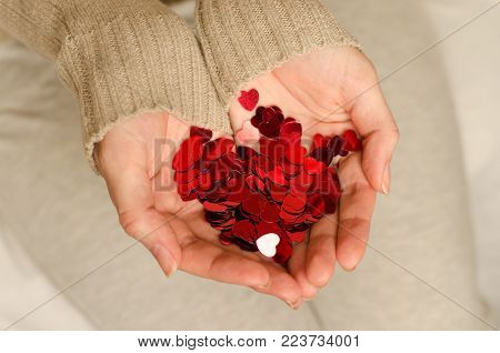 Hands of a young caucasian girl hold small hearts close up. Love and happiness are in our own hands