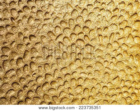 Molten metal background photograph in gold. Bright dimpled molten metal background of inverted bubbles in gold, shot outdoors in natural light. Abstract, unique and artistic textured backdrop.