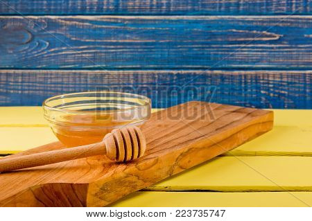 Honey in plate with wooden chopstick for honey on wooden background.