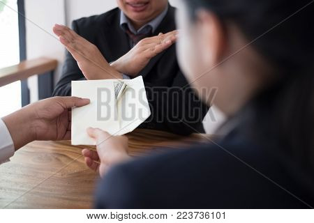 Businessman rejecting money cash banknote from business people.  honest man refuse to take the bribe. anti-bribery, corruption, venality concept.