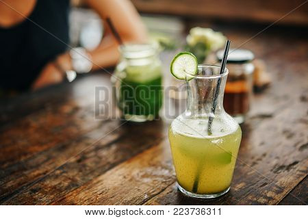 decanter with a fresh green drink of lemonade with a piece of lime on the neck. Refreshing drink.