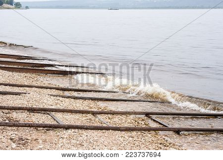 Rusty metal pipes and rails for descent of boats on the water on the coast of the Volga.