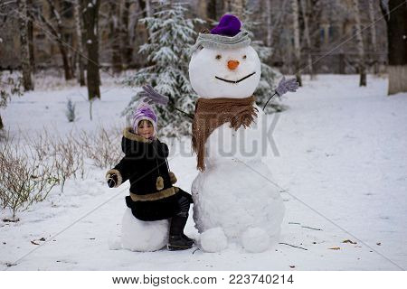 A little cheerful girl sits near big real funny snowman. A cute little girl has fun in winter park, wintertime