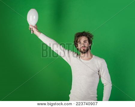 Man With Disheveled Hair Hold Big Lamp. Guy Has An Idea On Green Background, Morning. Power And Busi