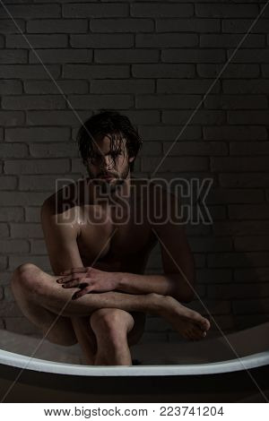 Guy With Wet Hair Sitting In Bath Tub. Man With Muscular Body In Bath. Spa And Relaxation, Sexy Man.