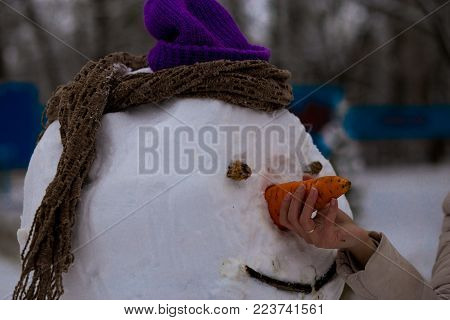 Woman's hand hold a big carrot, the nose of a real big snowman in winter park, wintertime