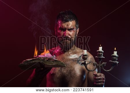 Hipster Man Hold Book And Candles Burning On Purple Background. Halloween Holidays Celebration. Wiza