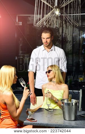Man With Sexy Girls In Bar On Summer Day. Twins Women Sensual Drink Champagne In Cafe Outdoor. Addic