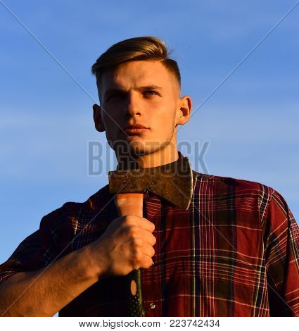 lumberjack guy with ax on blue sky background, camping. Wanderlust, hiking and travel. summer holiday and travel. man with axe, camping, hiking, suicide. Man lumberjack shaving with axe in sunset.
