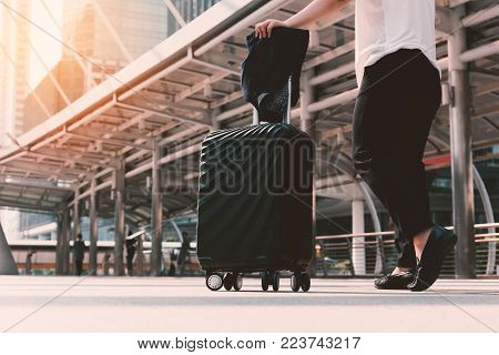 Asian woman walking to airport terminal with luggage. Business transportation and Flight Travel concept. Vacation and Lifestyle concept. Airport Bus and Train station theme.