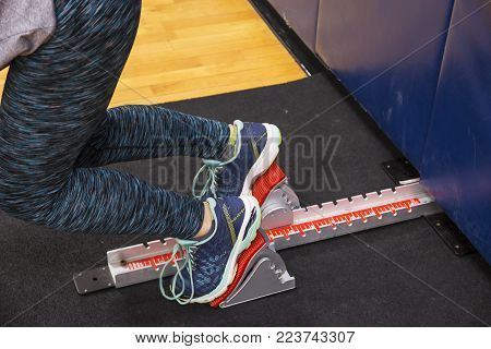 A sprinter getting sprint start practice using the starting blocks at night in the high school gym during winter track and field season.