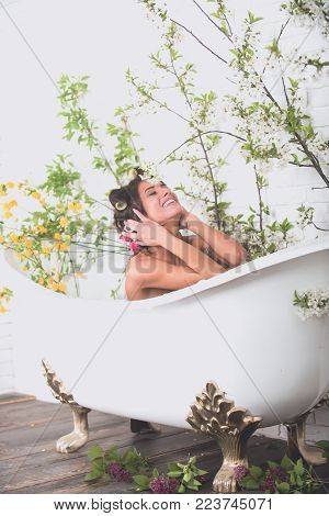 Beauty and spa, health, wellness. Spring relax in bathroom. Spa and hygiene, housewife, hairdresser. Woman with curlers on hair sit in bath, body care. Sexy woman in bathtub at spring blossom, spa.