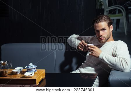 Tea party, ceremony, time. Brew tea concept. Relaxation, lounge, relax. Man drink tea on sofa in cafe. Beverage, food, cuisine.