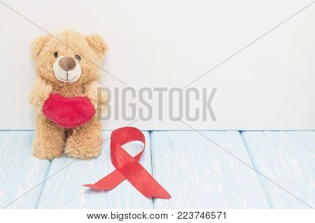 stetoscope, red heart and bear on blue background with red heart