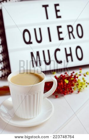closeup of a white ceramic cup with coffee on a table, a bunch of flowers and a lightbox in the background with the text te quiero mucho, I love you so much written in spanish