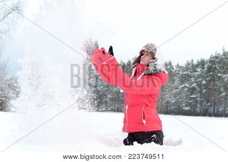Teenage girl in warm earflap playing with snow in winter forest. Inspirational colored vibrant outdoors horizontal wintertime image.