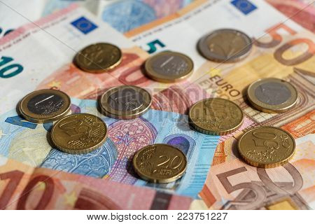 Euro coins and cents on banknotes of ten, twenty and fifty euros