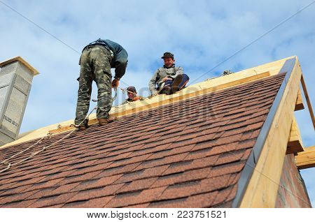 KYIV, UKRAINE - February, 05, 2018: Roofer laying asphalt shingles. Roofer with safety kit on the house roof installing, repair asphalt shingles.Roofing construction. Roofer's Kits for Fall Protection
