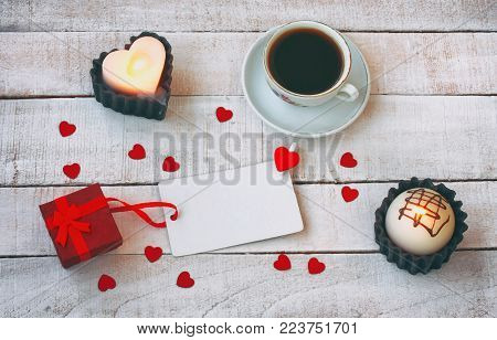 valentines day composition, cup of coffee, gift box, confetti heart shape, candle, blank paper tag on white wooden table, top view, flat lay