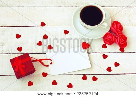 valentines day composition, cup of coffee, gift box, confetti heart shape, roses flowers, blank paper tag on white wooden table, top view, vintage style