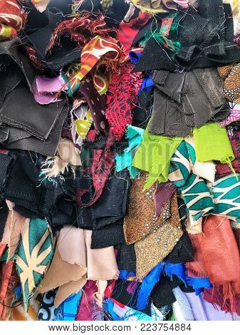 Colorful pieces of clothes stitched on top of each other to create a foot mat.