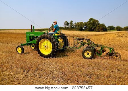 ROLLAG, MINNESOTA, Sept 2, 2017: An unidentified operator of an A john Deere tractor and two bottom plow are ready for field demonstrations at the annual WCSTR farm show in Rollag held each Labor Day weekend where 1000's attend.