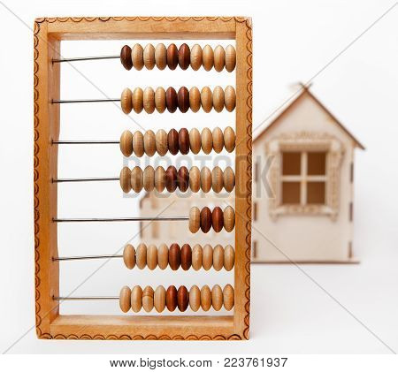 Wooden abacus stand against a small house