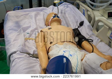 Medical robotic simulator on the hospital bed with artificial ventilation, drop counter and blood pressure monitor for training medical students