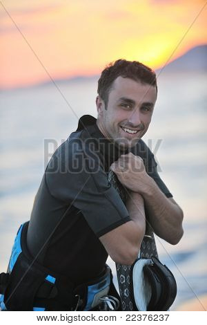 Portrait of a strong young  surf  man at beach on sunset in a contemplative mood with a surfboard