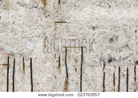 Berlin wall corroded concrete surface with rusty bars carcass