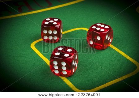 risk concept - playing dice on a green gaming table. Playing a game with dice. Red casino dice rolls. Rolling the dice concept for business risk, chance, good luck or gambling