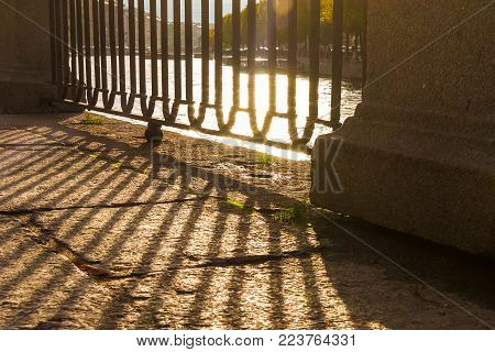 A grate of the fence of the granite embankment and its shadow on the pavement closeup in sunny day, Saint Petersburg, Russia