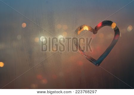heart, drawn on a misted window, against the backdrop of a night city street