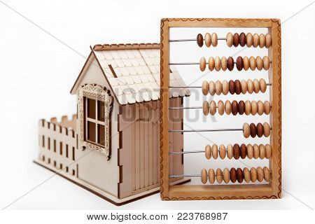 Wooden abacus stand next to a small house on a white background.