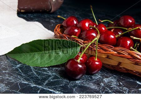 Several Red Sweet Cherries On The Table. Fresh Organic Cherry In Yellow Wooden Basket On Dark Marble