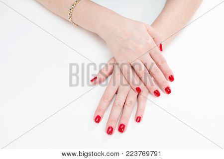 Female hands with manicure and red lacquer on a white table in the beauty salon. closeup of hand of a young woman