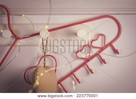 Pink Heart clothes hanger and heart shape hanger on red background. Valentines day concept