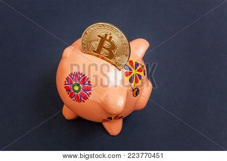 Piggy bank and golden bitcoin coin virtual money on black background. Cryptocurrency and saving concept. Electronic virtual money for web banking and international network payment