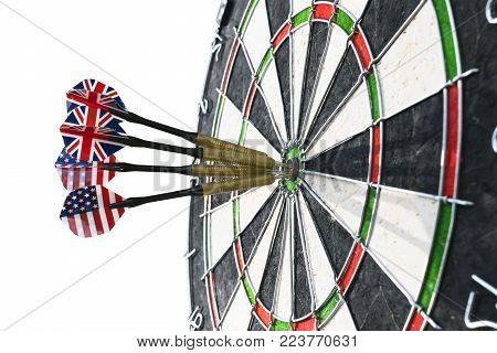 Metal darts have hit the red bullseye on a dart board. Darts Game. Darts arrow in the target center darts in bull's eye close up. isolated on white background.Success hitting