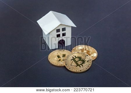 Toy house and coins bitcoin on black background. Cryptocurrency and saving concept. Electronic virtual money for web banking and international network payment
