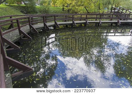 Reflection of the sky with clouds in the water surface of the pond. Trinity Pond, Academician Artsimovich Street,  South-Western District of Moscow, Russia. Sunny day in October.