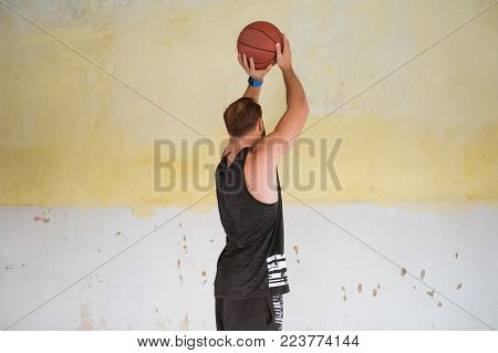 Young man basketball player with ball in hands jumping high