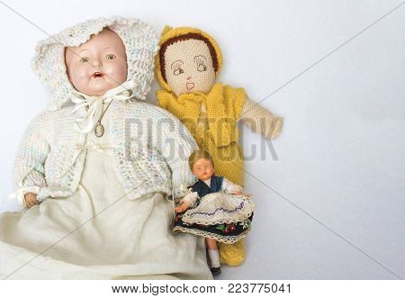 Trio of antique and vintage dolls on white background