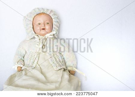 Antique china doll with knit sweater and cameo on white background