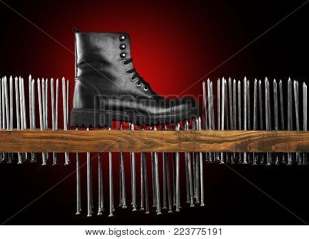leather black boot on black background with red backlight. The boot stands on the wooden board and pushes the nails. conceptual and creative shoe picture. Man Boot