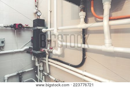 Plumbing valves with red faucets on the white plastic water pipes of center plumbing system with manometer and wall with ceramic tiles. Picture with tone effect