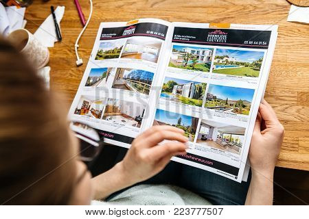 PARIS, FRANCE - APR 26, 2017: View from above of woman reading Houses and Apartments real estate catalogue with properties for rent and buy in France, Alsace Maisons Alsace