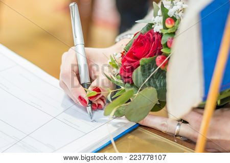 Wedding ceremony. Bride signing registration of marriage certificate. Woman choosing to take or reject husband's surname.