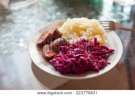 Meat sausage with potato puree and salad of beet