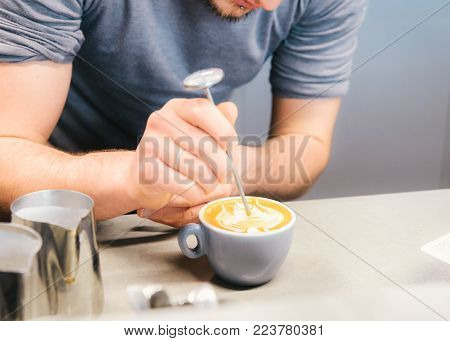 Barista using coffee machine preparing fresh coffee or latte art and pouring into white cup at coffee shop and restaurant, bar or pub.